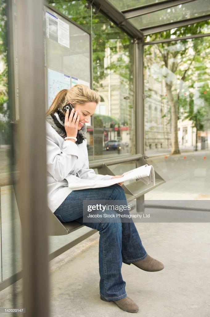 Hispanic woman using cell phone and waiting at bus stop