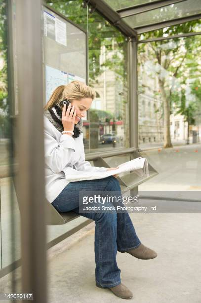 Hispanic woman using cell phone and waiting at bus stop
