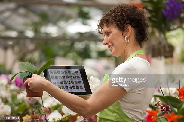 Hispanic woman using digital tablet in plant nursery