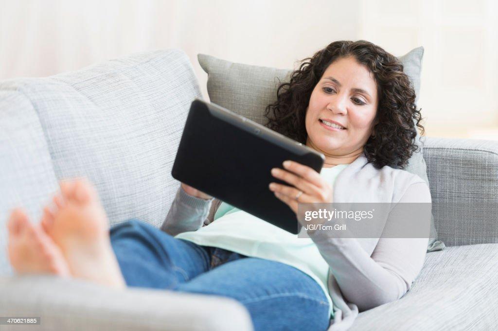 Hispanic woman using digital tablet on sofa : Stock Photo