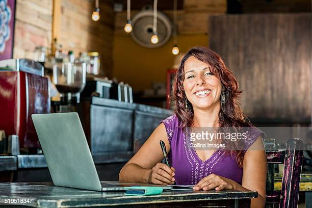 Hispanic woman using laptop in coffee shop