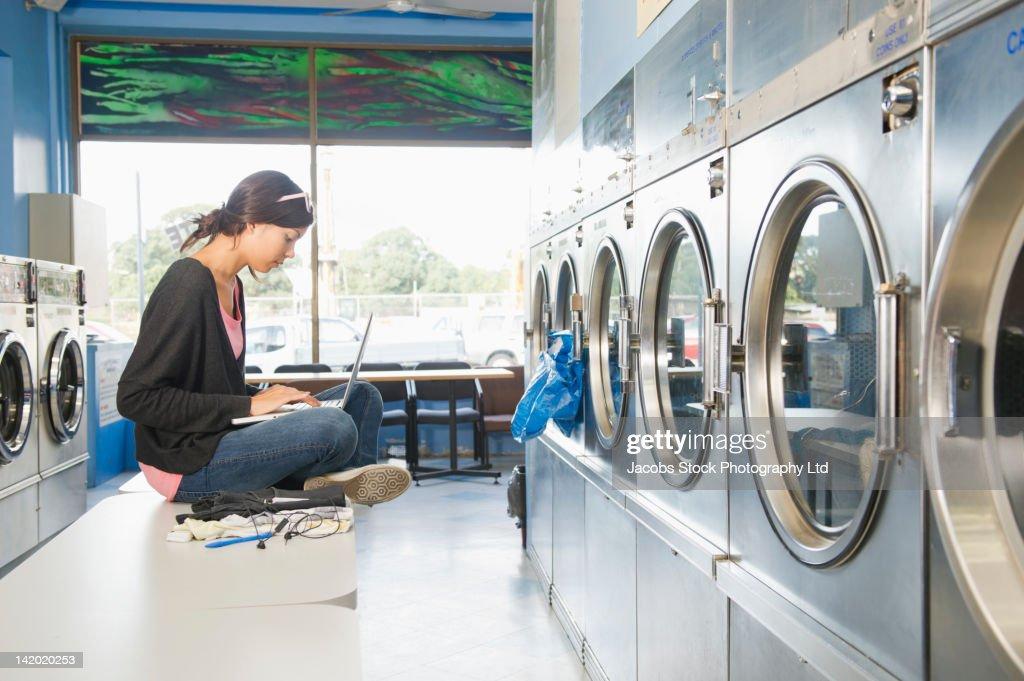 Hispanic woman using laptop in self-service laundry facility