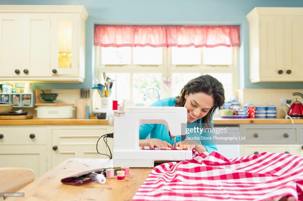 hispanic woman using sewing machine on kitchen table stock