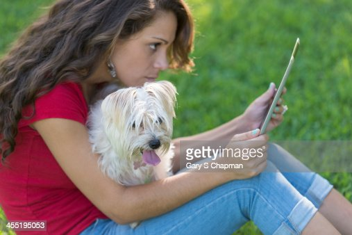 Hispanic woman using tablet with dog on lap : Stock Photo
