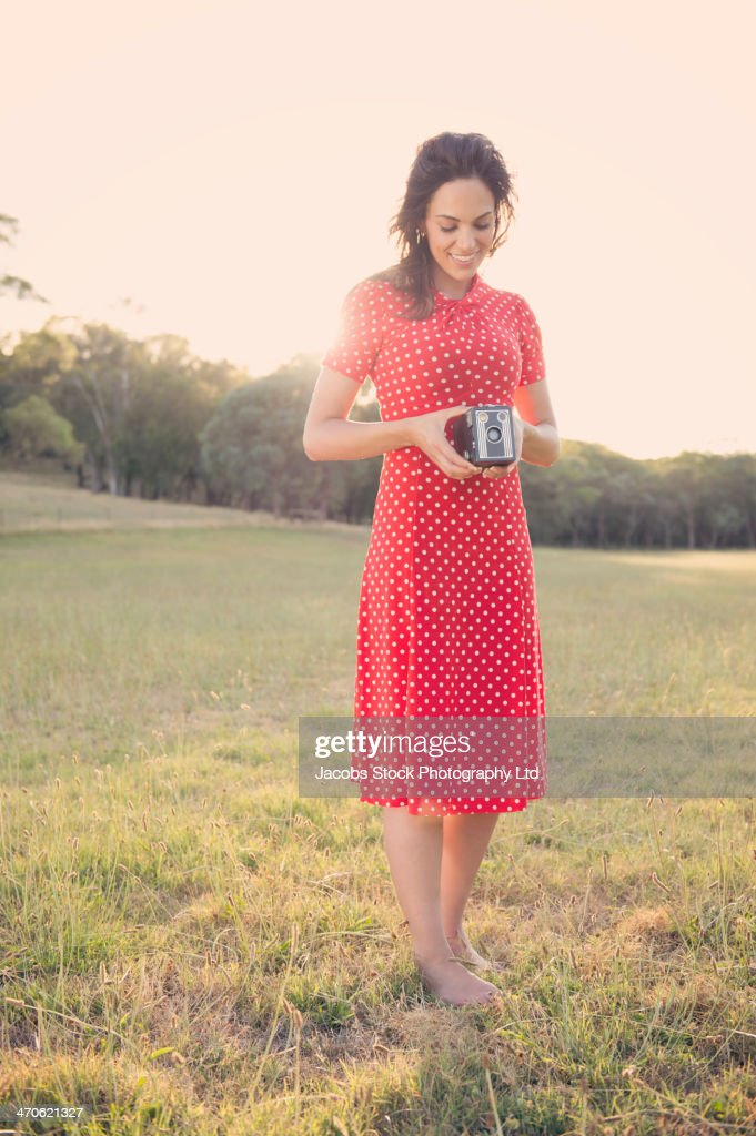 Hispanic woman using vintage camera : Stock Photo