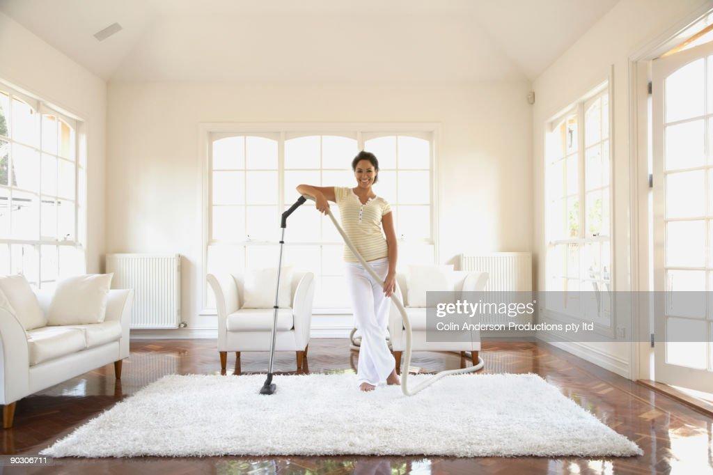 Hispanic woman vacuuming floor : Stock Photo