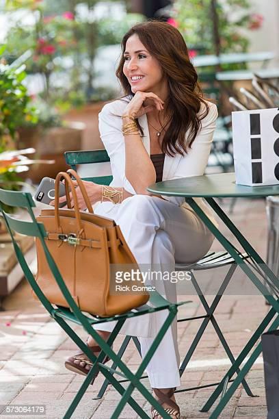 Hispanic woman waiting at patio table