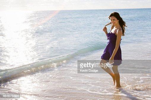 Hispanic woman walking in surf on beach