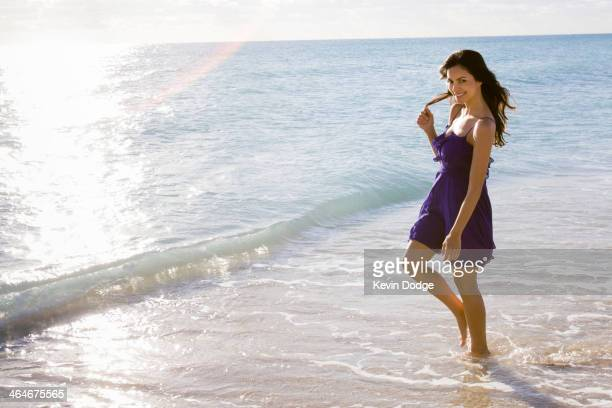 Hispanic woman walking in surf on beach