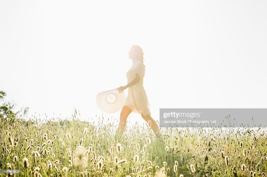 Hispanic woman walking in tall grass