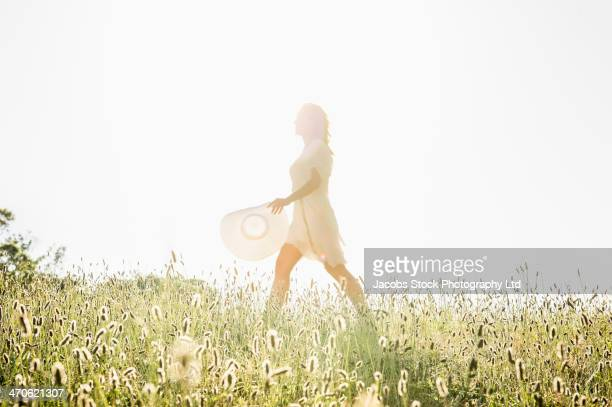 Hispanic woman walking in tall grass