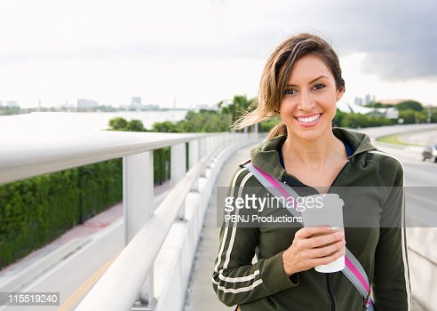 Hispanic woman walking outdoors with coffee : Stock Photo