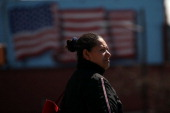 Hispanic woman walks down a street bearing a large painting of an American flag on March 28 2011 in Union City New Jersey Union City New Jersey one...