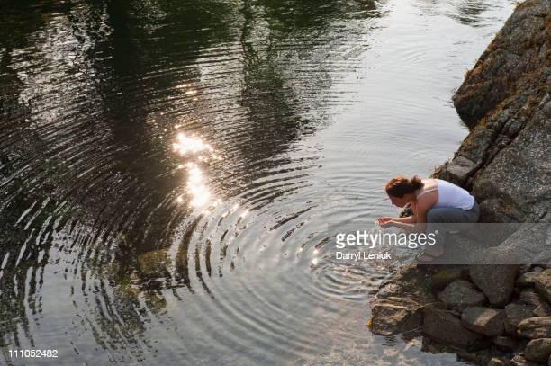 Hispanic woman washing face in lake