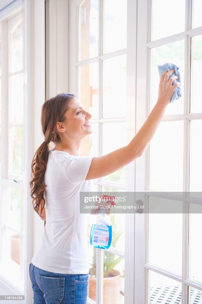 Hispanic woman washing windows : Stock Photo