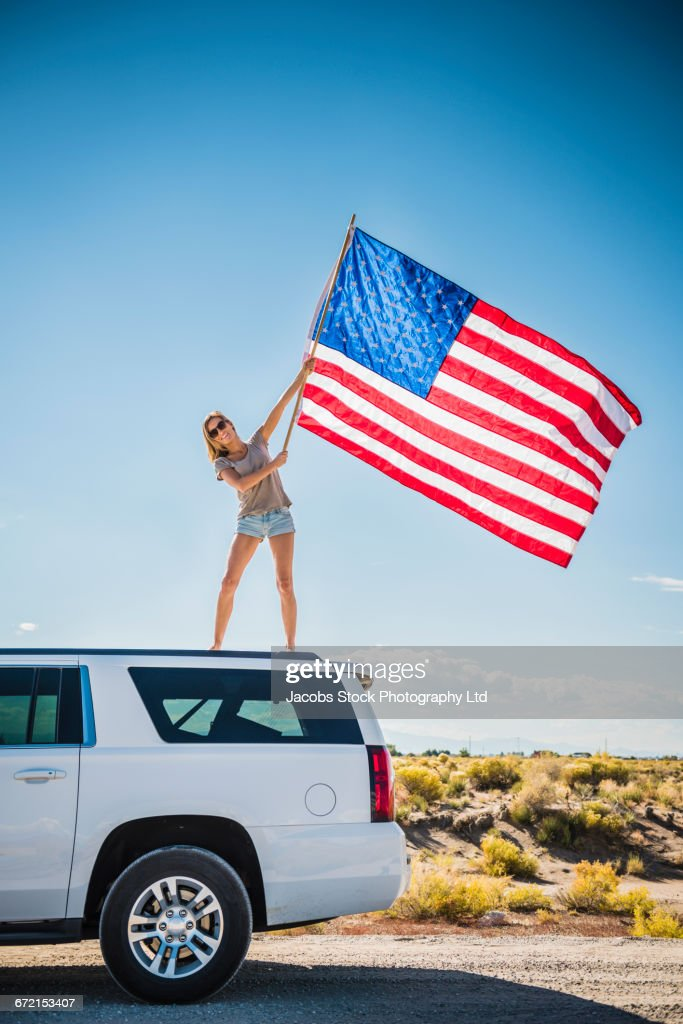 Hispanic Woman Waving American Flag On Roof Of White Suv Stock