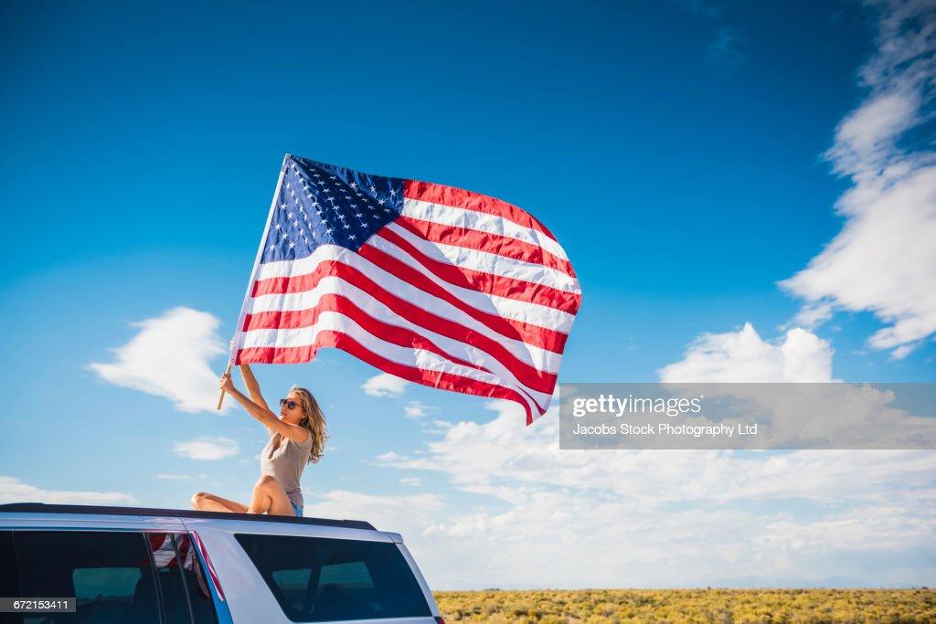Hispanic Woman Waving American Flag Sitting On Roof Of White Suv