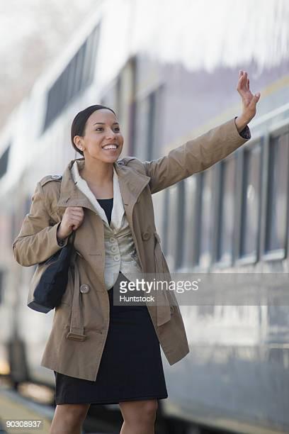 Hispanic woman waving goodbye at a railroad station platform