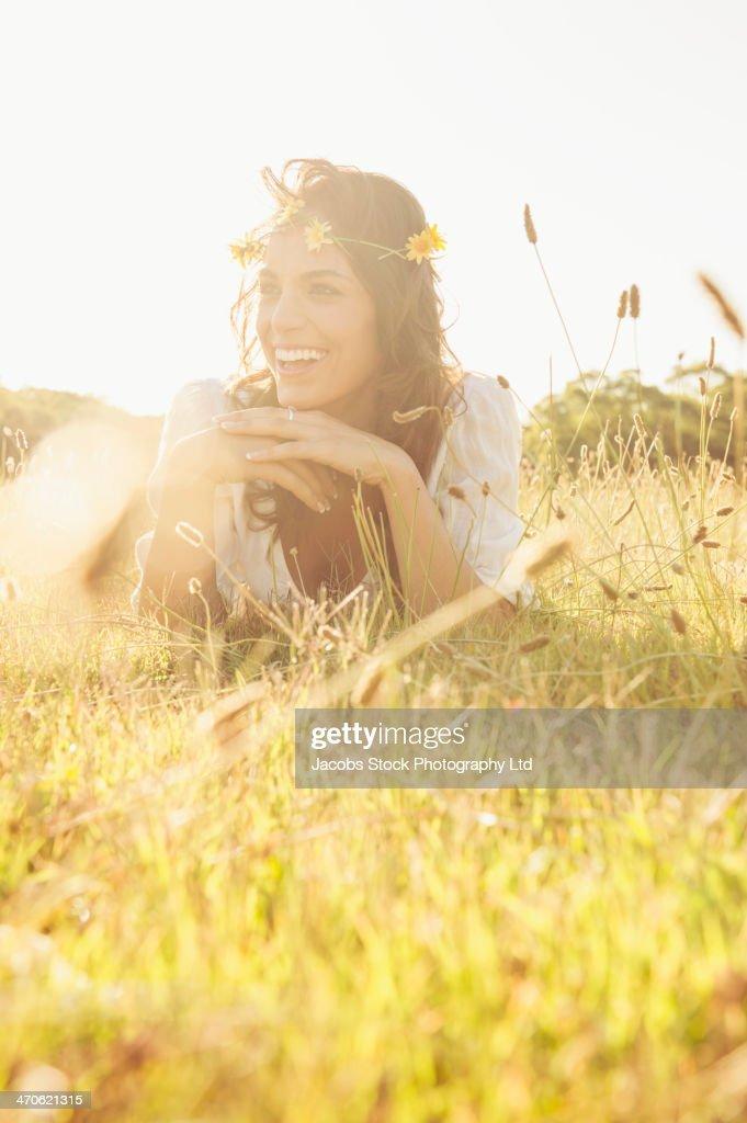 Hispanic woman wearing flower crown in grass : Stock Photo
