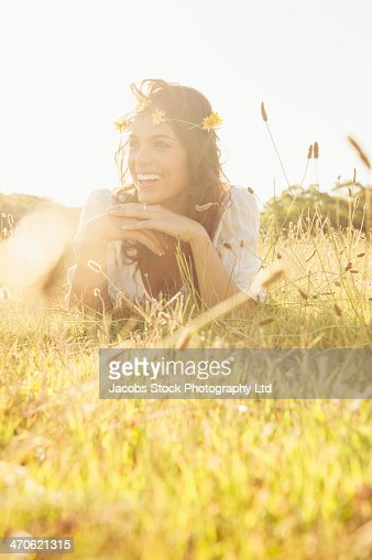 Hispanic woman wearing flower crown in grass : Stock Photo
