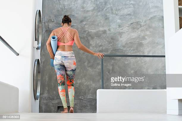 Hispanic woman wearing workout gear in modern living room