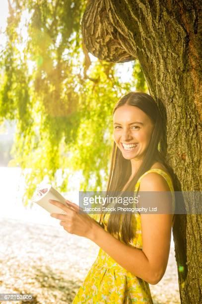 Hispanic woman wearing yellow dress leaning on tree reading book