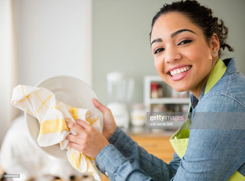 Hispanic woman wiping plate : Stock Photo
