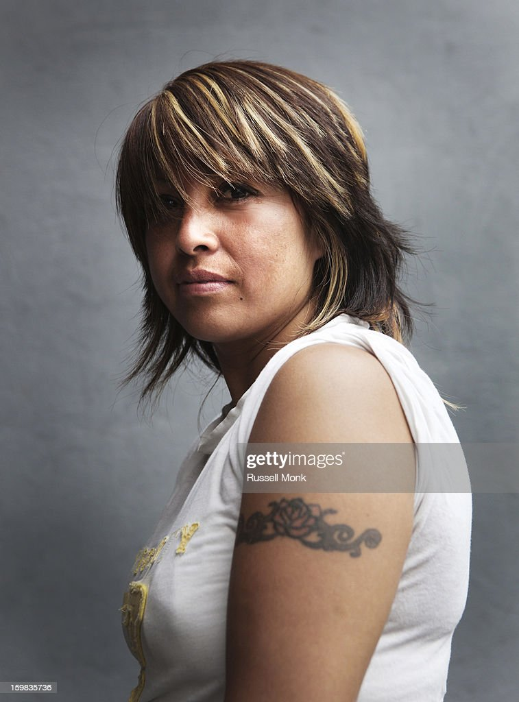 Hispanic woman with a tattoo on her arm. : Stock Photo