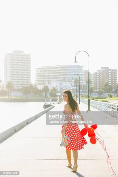 Hispanic woman with balloons on urban waterfront sidewalk