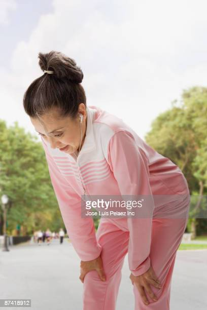Hispanic woman with headphones resting after exercise