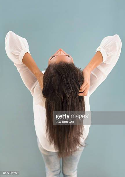 Hispanic woman with long hair leaning back