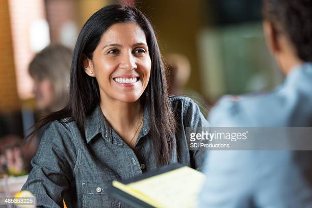 Donna ispanica con l'applicazione per riprendere il lavoro nel corso del colloquio riunione