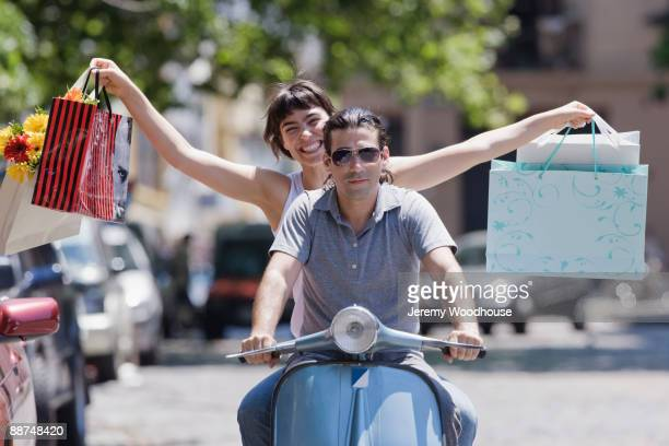Hispanic woman with shopping bags riding scooter with boyfriend