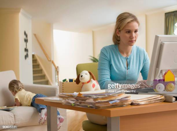 Hispanic woman working at computer with toddler in background