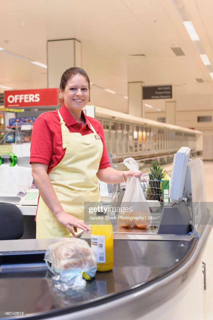 Hispanic woman working at grocery checkout : Stock Photo