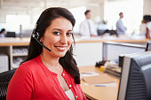 Hispanic woman working in a call centre smiling to camera