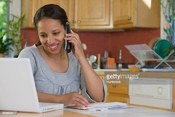Hispanic woman working on a laptop and talking on a mobile phone