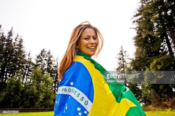 Hispanic woman wrapped in Brazilian flag