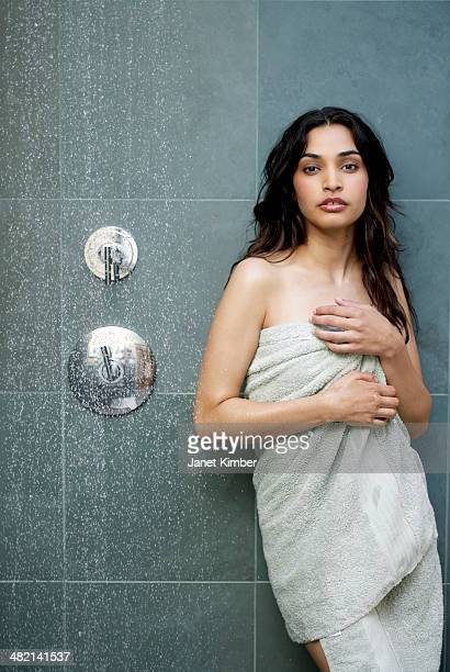 Hispanic woman wrapped in towel in bathroom