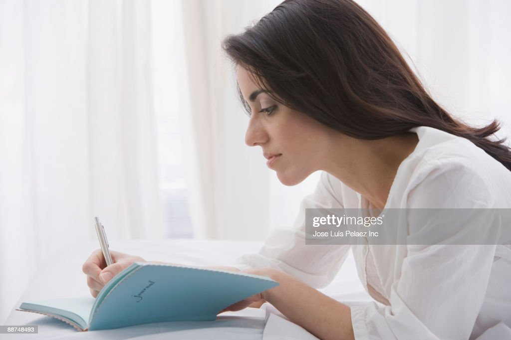 Hispanic woman writing in journal : Stock Photo