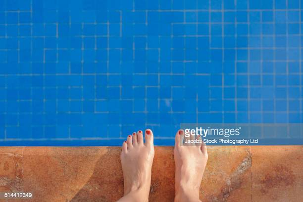 Hispanic woman's feet at edge of swimming pool