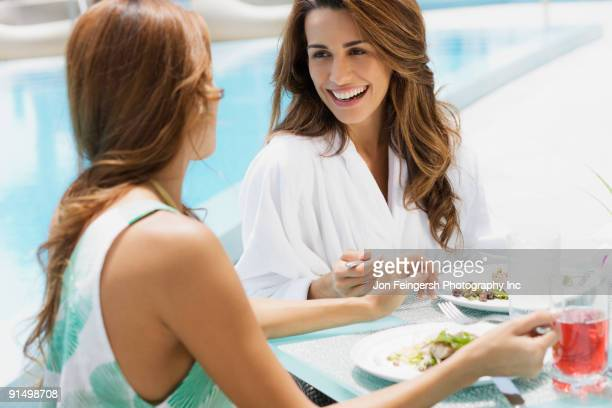 Hispanic women eating lunch poolside