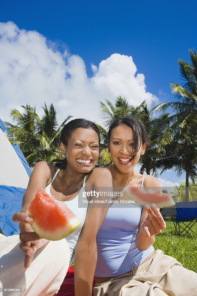 Hispanic women eating watermelon : Stock Photo