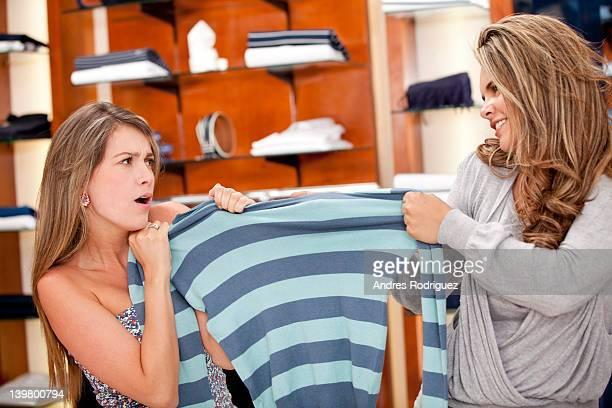 Hispanic femmes qui se battent pour la chemise en magasin