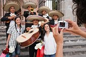Hispanic women having photograph taken with Mariachi band