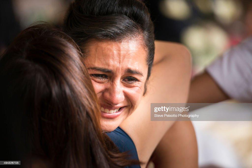 Hispanic women hugging and crying : Stock Photo