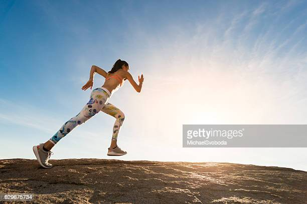 Hispanic Women Running Up A Granite Boulder