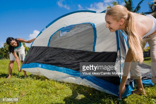 Hispanic women setting up tent : Bildbanksbilder