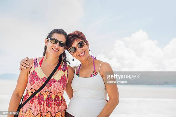 Hispanic women smiling together on beach