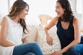 Hispanic women talking on sofa